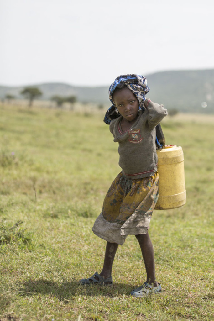 A small girl struggles to carry a heavy load of water to her home.