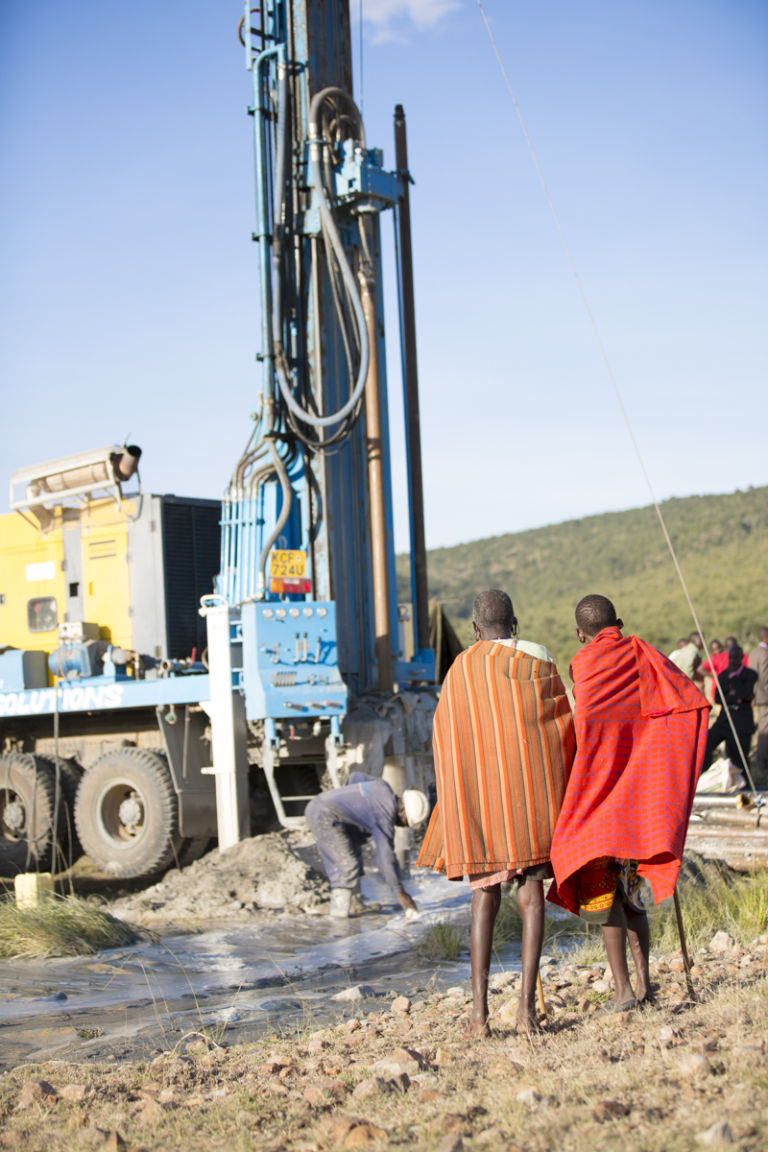 Elders look on as MOM drills a water well at Ilturisho Kenya
