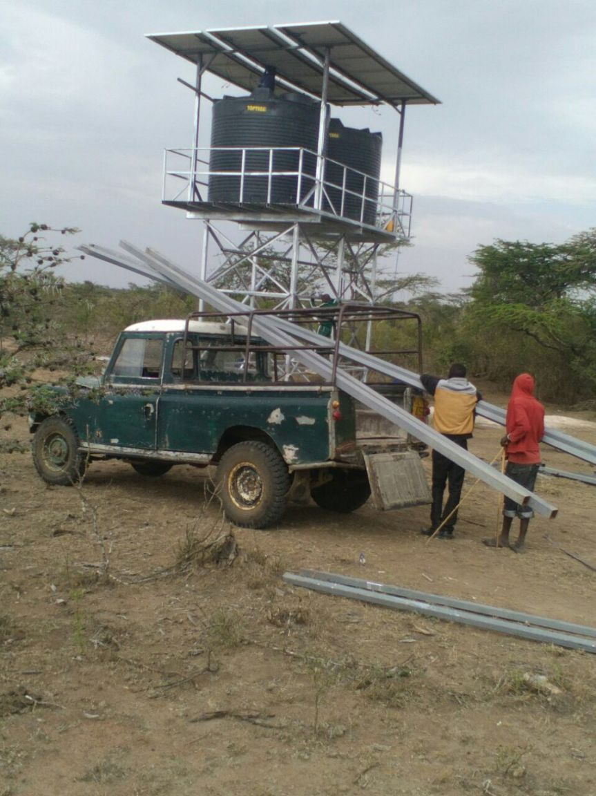 The crew works to install the solar panels that will power the pump at the borehole. Water quality and water scarcity is a serious problem in the Maasai Mara area of Kenya. We partner with local communities to provide clean water.
