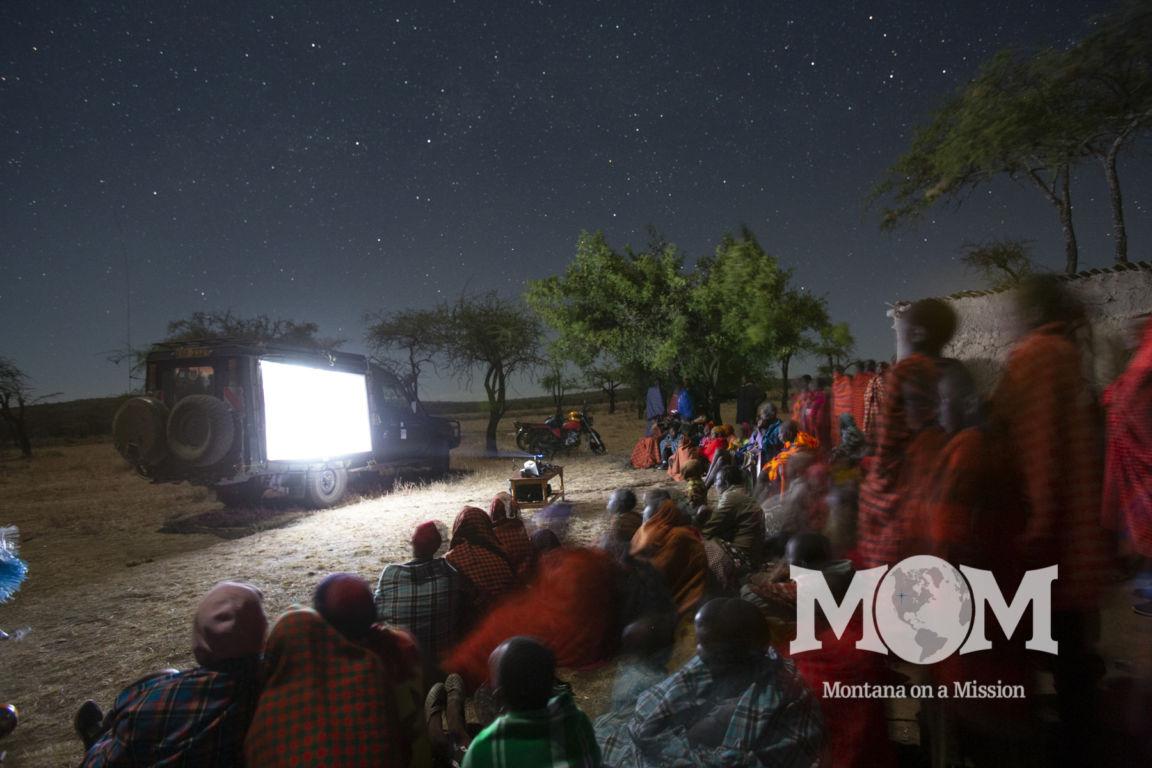Maasai families gather to watch the story of Jesus in their own language for the first time. Montana on a mIssion partners with Life Ministries to share the word of God through the